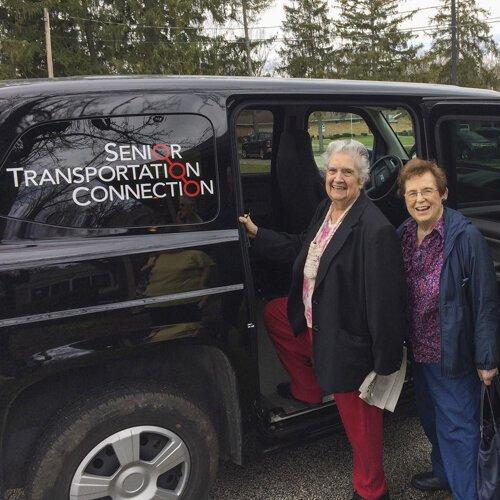 An STC driver helps a senior passenger board an STC bus.